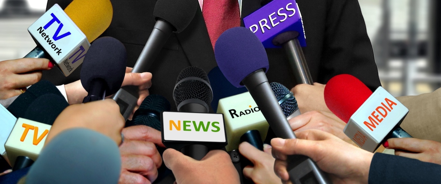 Media and press interview with group of journalists surrounding VIP